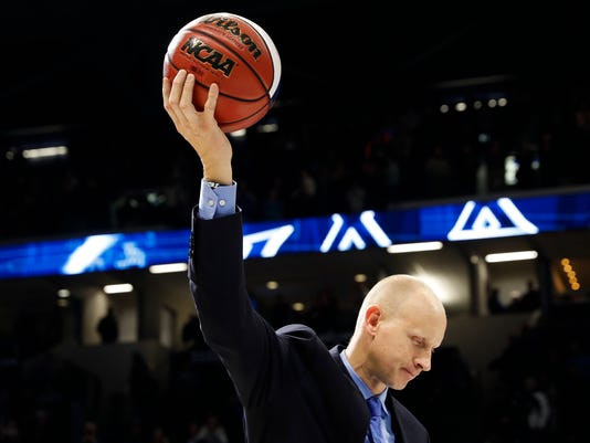 Xavier head coach Chris Mack holds a commemorative game ball after becoming the winningest coach in Xavier history after an NCAA college basketball game against St. John's, Wednesday, Jan. 17, 2018, in Cincinnati. Xavier won 88-82. (AP Photo/John Minchillo)