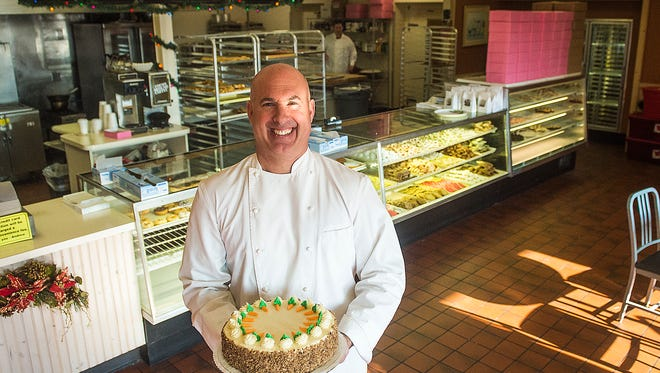Andrew Swartz, owner of Andrew's Pastries, poses for a portrait in his business with a carrot cake. Andrew's Pastries celebrated its 20th anniversary Monday.