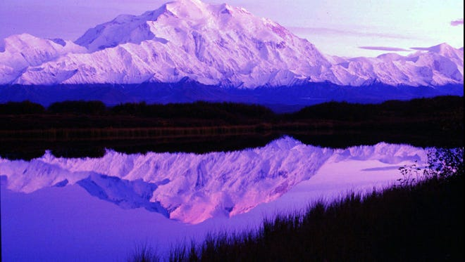 The sun sets as Mt. McKinley casts its reflection on Reflection Pond at the west end of Denali National Park road a few miles east of Camp Denali in Denali Park, Alaska.