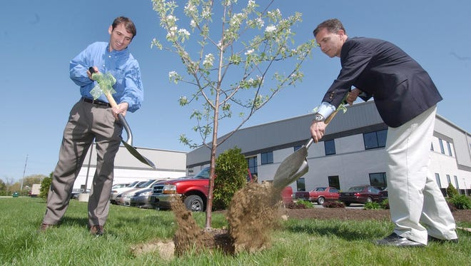 Speakman Co. president Rodman Ward, left and Charles Copeland (blazer) plant a Earth Day tree in honor of their late CEO, Willard Speakman.