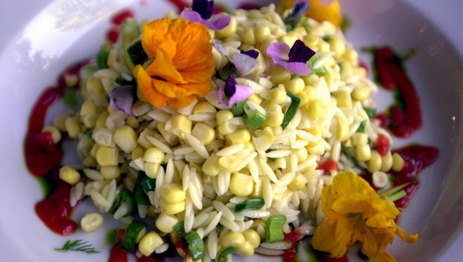 Orzo pasta is served with fresh corn, roast red peppers, sweet pea blossoms and nasturtiums.