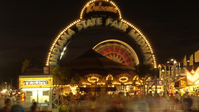 An illuminated arch welcomes visitors to the bright lights of the midway at the Indiana State Fair. John Severson/ The Star GENERAL INFORMATION: Wednesday, Aug. 6, 2003. Slug: Fairlights. Assignment #87187. By John Severson. The State Fair After Dark.