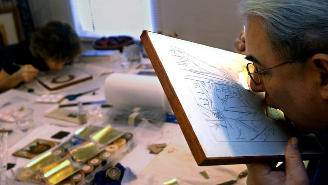 For more than 15 years, Father Richard Cannuli has been coming to Vero Beach in the winter to teach an intensive five-day course in icon painting for the Center for Spiritual Care. In this file photo,  Cannuli breathes on the red clay to create condensation before applying a piece of gold leaf to a student's Icon. Although breathing on the clay helps adhere the gold leaf, it  also symbolizes God breathing life into Adam by giving breath and life to the icon.