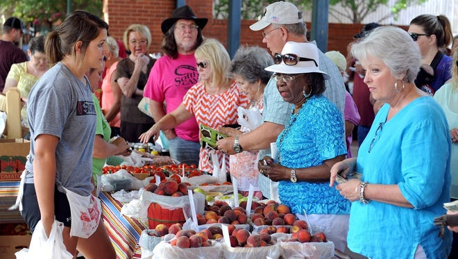 Customers peruse the peach choices during Peach Day at the Wichita Falls Downtown Farmers Market in 2014.