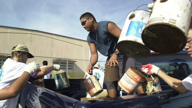 In this 2002 file photo, Robert Castaneda of Santa Rita unloads buckets of paint from his truck with the help of volunteers during the Hasso Guam household hazardous waste collection at Tiyan.
