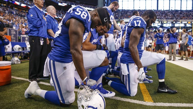 Colts teammates kneel together during the national anthem before they face off against the Cleveland Browns at Lucas Oil Stadium on Sept. 24, 2017.