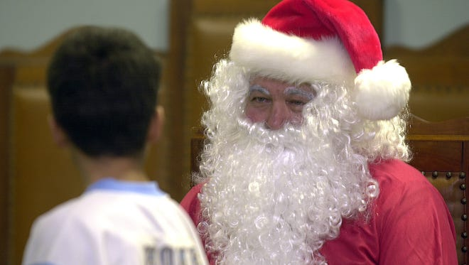 Billy Ray Jones sits in for the real Saint Nick at Santa's Helpers Christmas Party for foster children at the Masonic Lodge in Jackson in this 2003 file photo.
