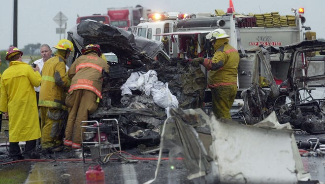 Rescue workers remove the bodies from a van that crashed and burned after being struck by a tractor-trailer on State Road 60 near the Kissimmee River Bridge near Indian Lake Estates, Fla., Friday, June 4, 2004. The five dead occupants of the van were all students or former students of Crown College in Knoxville, Tenn.  Their names were Darci Brown, 22, her husband, Aaron Brown, 21, David Childers, 21, Jonathon Pinkerton, 18, and Brad Askew, 22. The driver of the tractor-trailer was taken to Orlando Regional Medical Center where he later died.  (AP Photo/Tampa Tribune, Greg Fight)