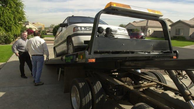 A tow truck driver loads a car in 2001 in Peoria.