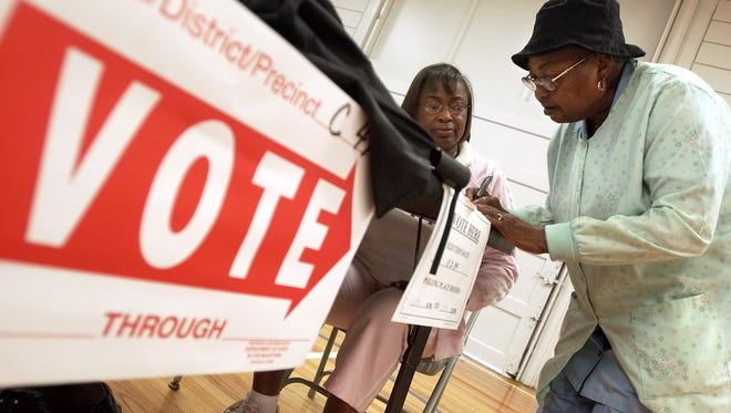 Voters sign in to vote at at Acadian Elementary School in 2004.