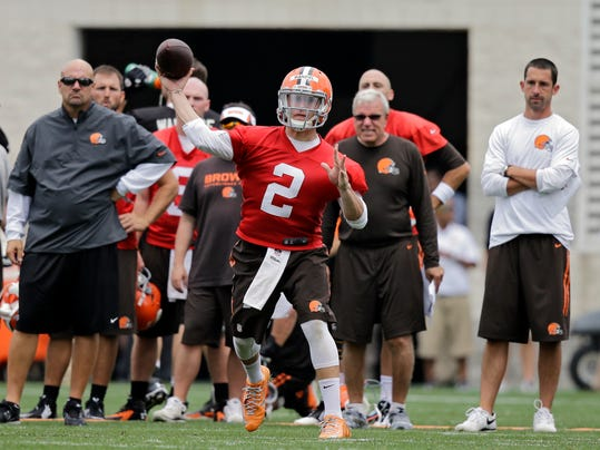 Cleveland Browns quarterback Johnny Manziel (2) fires a pass as head coach Mike Pettine, left, and offensive coordinator Kyle Shanahan, right, watch, during team drills at the NFL football team's training camp in Berea, Ohio, Sunday, July 27, 2014. (AP Photo/Mark Duncan)