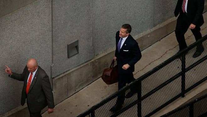 Flanked by security guards, Missouri Gov. Eric Greitens, center, arrives at court for jury selection in his felony invasion of privacy trial, Thursday, May 10, 2018, in St. Louis. Greitens is accused of taking an unauthorized and compromising photo of a woman with whom he had an affair.