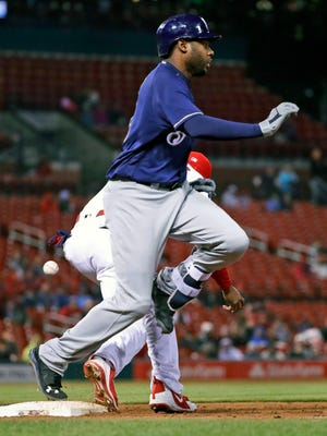 Lorenzo Cain is safe at first as the ball gets away from St. Louis Cardinals first baseman Jose Martinez in the ninth inning Monday night. The two get their legs tangled, went down in pain and left the game.