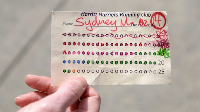 As students prepare for Awesome 3000, the number of laps they run is recorded on these running club cards at Harritt Elementary School in West Salem.