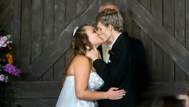 In this Sunday, Jan. 28, 2018, file photo, Dustin Snyder, 19, kisses his wife, Sierra, after exchanging wedding vows at the The Big Red Barn in Plant City, Fla. Dustin Snyder, who had been battling a rare form of cancer has died less than a month after marrying his high school sweetheart.
