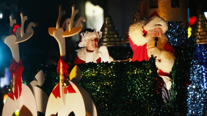 Santa and Mrs. Claus ride a float down College Avenue during the 44th Annual Downtown Appleton Christmas Parade.