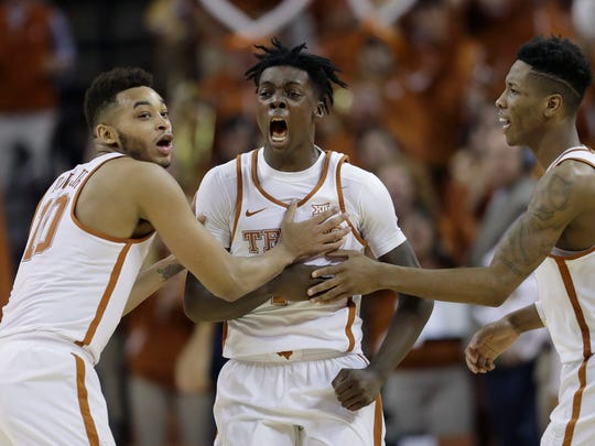 FILE - In this Jan. 23, 2017, file photo, Texas guard Andrew Jones, center, celebrates with teammates Eric Davis Jr. (10) and Kerwin Roach Jr. (12) after he hit the winning shot against Oklahoma in the second half of an NCAA college basketball game, in Austin, Texas. Through each game since early January, win or lose, the Texas Longhorns have insisted teammate Andrew Jone has been with them every step of the way as they their fought to return to the NCAA Tournament. So much so, that when it came time to see if their name would be called, the Longhorns dialed up Jones, who is in Houston for leukemia treatments, on a video conference call to listen and watch together. (AP Photo/Eric Gay, File)