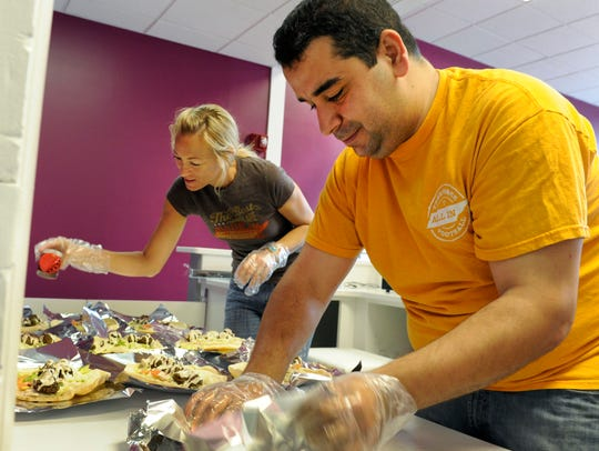 Yassin Terou, right, and his assistant Tiffany Teague prepare falafels and hummus for a catering job. Terou opened Yassin's Falafel House located at the corner of Walnut and Church streets in downtown Knoxville.