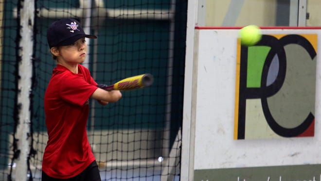 Jace Ethridge, 12, connects during batting practice while attending the Wounded Warrior Amputee Softball Team's Kids Clinic on Wednesday. Veterans who are amputees work with children with missing limbs.