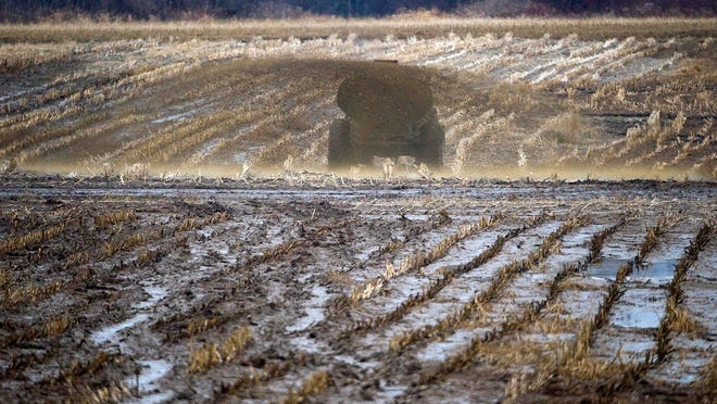A farmer distributes manure on a cornfield. Reducing runoff from farms is a target in efforts improving water quality.