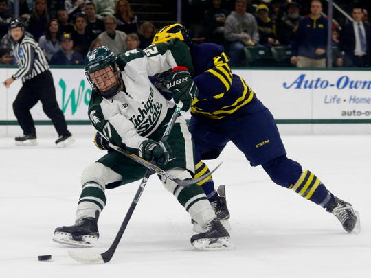 Michigan State's Matt Berry, left, and Michigan's Nolan De Jong battle for the puck during an NCAA college hockey game, Friday, March 13, 2015, at Munn Ice Arena in East Lansing, Mich.