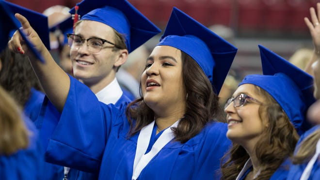 Graduate Melissa Placencio shows her friends where her family is seated at the 2017 Las Cruces High School commencement held on May 20, 2017.