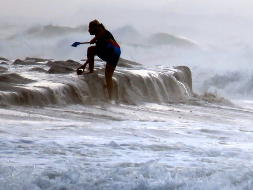 A person out looking for shells is surprised by a wave