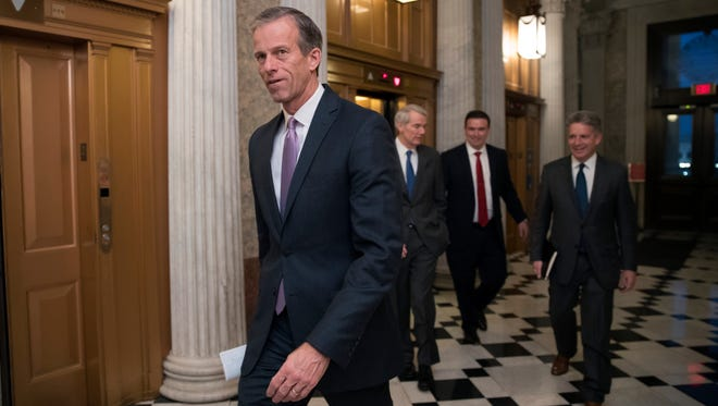 Sen. John Thune, R-S.D., the Republican Conference chairman, followed by Sen. Rob Portman, R-Ohio, second from left, a member of the tax-writing Senate Finance Committee, head to a closed-door meeting as Republicans in the House and Senate plan to pass the sweeping $1.5 trillion GOP tax bill on party-line votes, at the Capitol in Washington, Monday, Dec. 18, 2017. (AP Photo/J. Scott Applewhite)