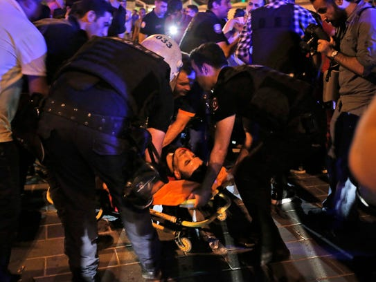 An injured man is attended by police when Turkish forces
