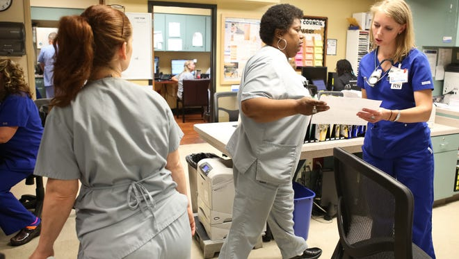 Registered nurse Marie Honeycutt, right, takes paperwork from Tonia McDonald in the Norton Hospital emergency room Monday. Emergency rooms have seen more patients in the wake of Obamacare.