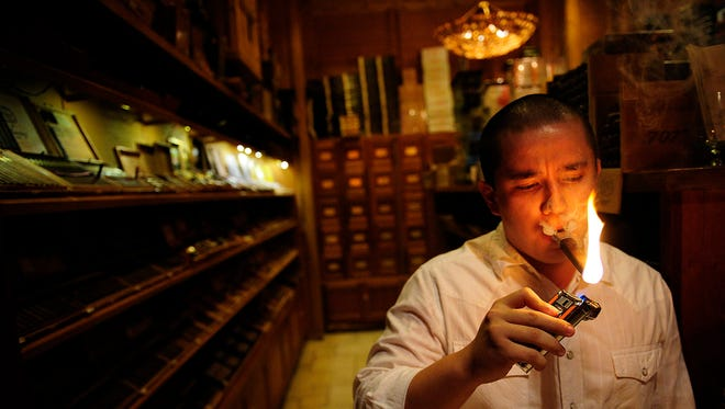 "Humidor manager Jonathan Hidalgo lights up a cigar Thursday, June 5, 2014 at Burn by Rocky Patel, a premiere cigar lounge and bar in Naples, Fla. As the federal government prepares for even tighter regulation of tobacco products, it's considering whether to cut cigar smokers some slack. The Food and Drug Administration is acting in the face of the rising popularity of electronic cigarettes and concerns over kids getting into the habit known as ""vaping."" At the same time, the feds question whether certain smokes merit their attention and are seeking public feedback until July 9 on whether to exempt fine cigars. (Corey Perrine/Staff)"