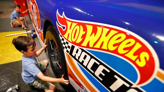 Jack and Henry Evers play at the Children's Museum of Indianapolis, in the Hot Wheels exhibit, Thursday, June 28, 2018.  They work to help raise awareness of cancer, in memory of a boy from their community, Brooks Blackmore, who died from brain cancer in May 2016.  The Evers family takes baggies with Hot Wheels, one of Brooks' favorite toys, and a card talking about Brooks and his cancer, and leaves the baggies in locations around the world in Brooks' memory.