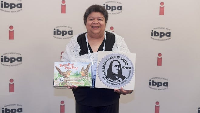 """University of Wisconsin-Stevens Point graduate and former Wausau School District educator Wanda Obermeier shows off her recently awarded Independent Book Publishers Association Benjamin Franklin Award for her children's book, """"Mama Bird Papa Bird."""""""