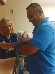 Janice Burke passes a newborn baby to a parent. Burke retired from Community Medical Center after 46 1/2 years working in the nursery.