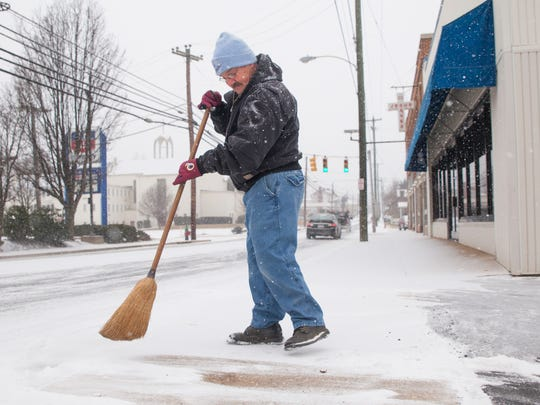 Wayman Brock Jr., who has been working at S&W Home Appliance for over 10 years, sweeps snow from in front of the Staunton business Monday, Feb. 16, 2015.