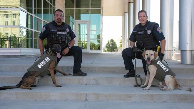 Pueblo County Sheriff's Office Dep. Benito Martinez, left, with K9 Edo and Deputy Sam Wolfe with K9 Mondy pose with new body armor equipment supplied to the two four-legged deputies for protection.