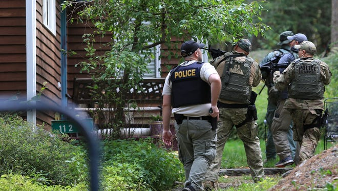 Pennsylvania State Police troopers and U.S. Marshals investigate and clear homes in the search for suspect Eric Frein, Wednesday, Sept. 24, 2014 in Canadensis, Pa.