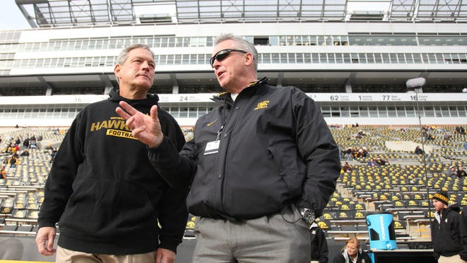 Iowa  coach Kirk Ferentz of the Iowa Hawkeyes visits with athletic director Gary Barta. Barta is pushing a bold facilities plan for an updated Kinnick Stadium and a new residence hall aimed at student-athletes.