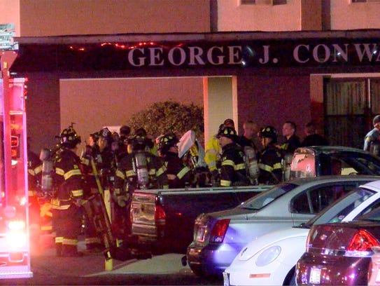 Firefighters are shown outside the George Conway Apartments