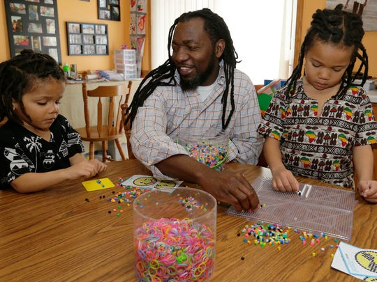 """Mushe Subulwa helps his sons Mooka, 7, and Mwakamui, 3, sort beads Saturday, April 7, 2018, at their Oshkosh home. Subulwa, who immigrated to the U.S. from Zambia 20 years ago, was one of the subjects in the FIT Oshkosh photo project. Subulwa, his wife, Ang, and their two children Mooka, 7, and Mwakamui, 3, live in Oshkosh. The photo exhibit, """"Color-Brave Photo Project: Black and Brown Faces, a New Narrative,"""" celebrates the lives of people of color in the Fox Valley. It will be on display April 20-25 in the Carriage House at the Paine Art Center and Gardens in Oshkosh."""