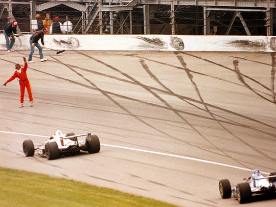 In this May 24, 1992, photo, track workers clean up debris and one man directs cars after a series of crashes in Turn 2 during the 76th running of the Indianapolis 500. The man directing cars is not Steve Wissen, who had a terrifyingly close call with Buddy Lazier's car during this race.