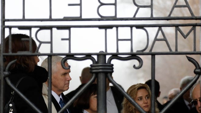 """U.S. Vice President Mike Pence, his wife Karen and his daughter Charlotte, from left, stand behind the gate with the infamous writing """"Work sets you free"""" as they visit the former Nazi concentration camp in Dachau near Munich, southern Germany, Sunday, Feb. 19, 2017, one day after he attended the Munich Security Conference. (AP Photo/Matthias Schrader)"""