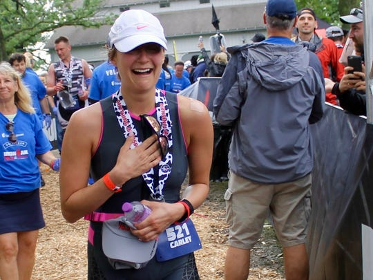 Carley Guzikowski,24, of Wauwatosa clutches her chest as she sees her longtime boyfriend Nate Renner on one knee at the end of the Ironman race in Madison, WI on June 10.