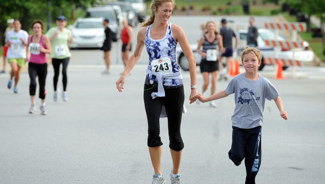 Janet Sword and her son Grayson, 11, cross the finish line together at a past Ramble Run 5K. Though this race has ceased, there are many other 5K races in Asheville this weekend.