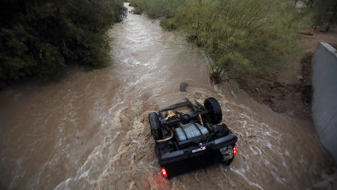 Water rushes around a vehicle near S. Elizabeth Drive and W. Lincoln Street after a storm, Tuesday, July 28, 2015, in Tucson. The occupants of the vehicle made it out safely.