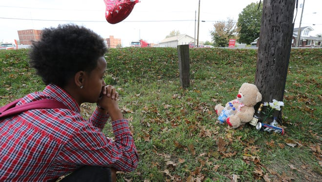 "Tekia Derksen stops at a memorial for Deshawndre Davis, 22, who was killed in the 3100 block of Dixie Highway.  ""He was more like a brother than a friend,"" said Derksen and friend, Jay McAfee, 16, who was also paying his respects.
