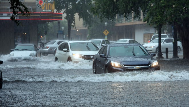 Motorists navigate many flooded streets in downtown Pensacola after heavy rains fell on the area the morning of Aug. 1, 2017.