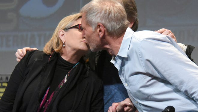 "In this July 10, 2015, file photo, Carrie Fisher, left, and Harrison Ford kiss at the Lucasfilm's ""Star Wars: The Force Awakens"" panel on day 2 of Comic-Con International in San Diego, Calif. Fisher revealed in an interview with People magazine published online on Nov. 15, 2016, that she had an affair with Ford during the filming of the 1977 film, ""Star Wars."""