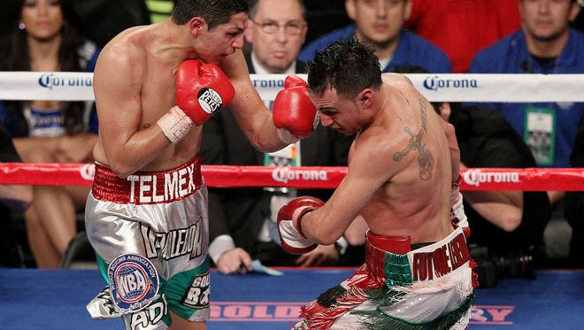 Pablo Cesar Cano (left) exchanges punches with  Paulie Malignaggi during their WBA Welterweight title fight at the Barclays Center on October 20, 2012 in the Brooklyn borough of New York City.  (Photo by Alex Trautwig/Getty Images)