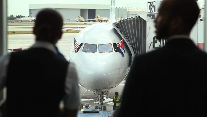 Employees at Miami International Airport watch as an American Airlines plane prepares to take off for Cuba on Sept. 7, 2016.